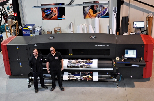 Manager Johan Ceuleers and large format print operator Jasper Corne, in front of the EFI VUTEk® GS3250LXr Pro roll-to-roll printer
